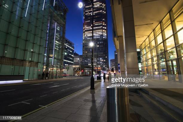 illuminated road amidst buildings in city at night - conor stock pictures, royalty-free photos & images