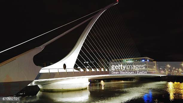 Illuminated Samuel Beckett Bridge Over Liffey River At Night