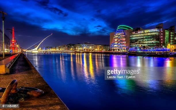 Illuminated Samuel Beckett Bridge Over River Against Sky