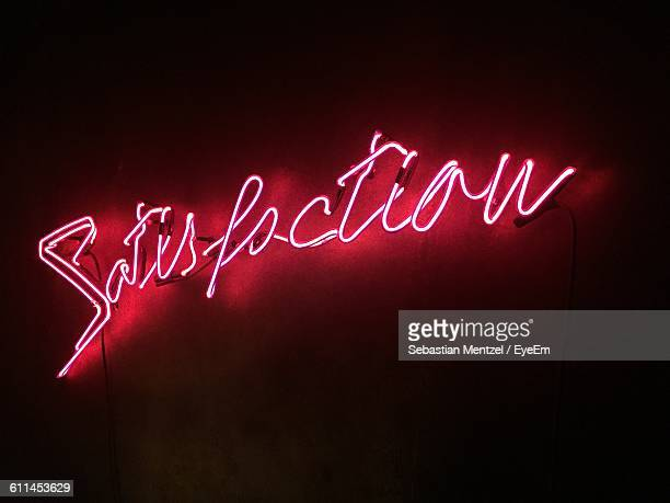 illuminated satisfaction text on wall at night - neon letters stock photos and pictures