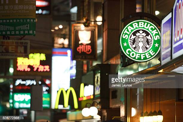 Illuminated shop signs at night in Tokyo including Starbucks and McDonald's