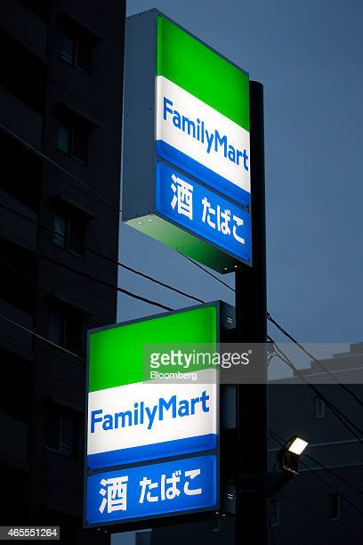 Illuminated signage for FamilyMart Co stands outside one of the company's convenience stores at dusk in Tokyo Japan on Saturday March 7 2015...