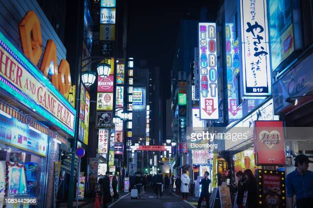 Illuminated signs are displayed on the exterior of commercial buildings at night in the Shinjuku district of Tokyo, Japan, on Wednesday, July 21,...