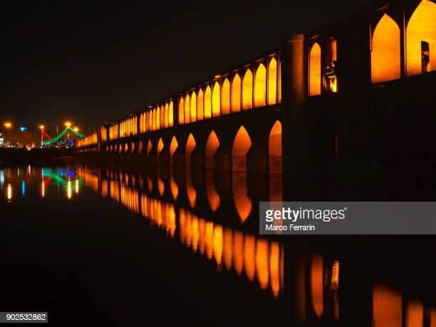 illuminated si-o-se-pol bridge at night, with beautiful reflection in zayandeh river, in the historic city of isfahan, iran - ザーヤンド川 ストックフォトと画像
