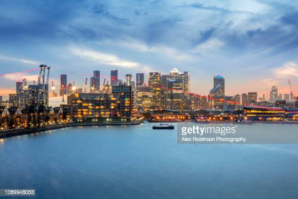 illuminated skyline of the london docklands financial district showing the o2 arena, emirates cable car and the victoria dock - the o2 england stock pictures, royalty-free photos & images