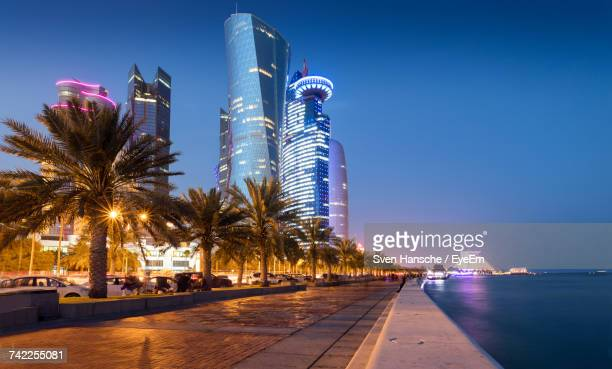 illuminated skyscrapers against blue sky at night - qatar fotografías e imágenes de stock