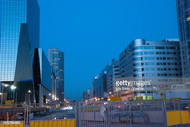 Illuminated Skyscrapers Against Clear Blue Sky In City