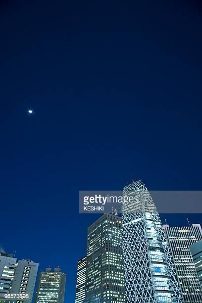 Illuminated skyscrapers against night sky with moon. Shinjuku-ku, Tokyo Prefecture, Japan