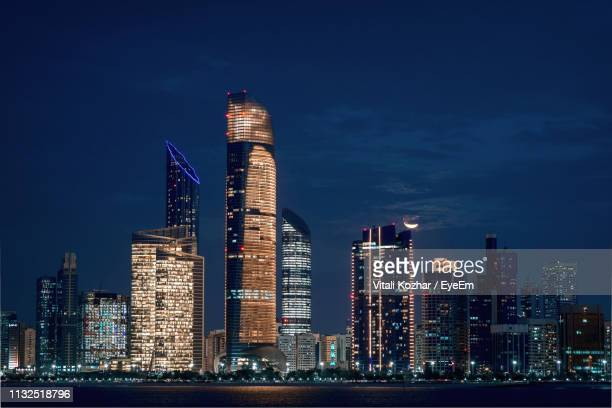 illuminated skyscrapers in city at night - abu dhabi stock pictures, royalty-free photos & images