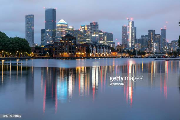 illuminated skyscrapers reflecting on thames river at dusk, canary wharf, london, uk - clear sky stock pictures, royalty-free photos & images