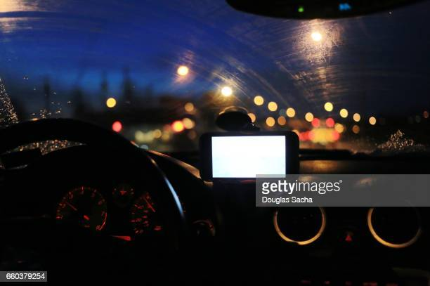 illuminated smartphone used as a navigation gps in a dark vehicle - dashboard camera point of view stock photos and pictures
