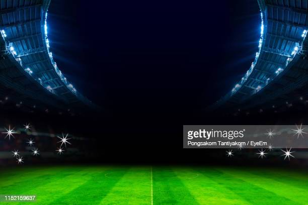 illuminated soccer field at night - stadion stockfoto's en -beelden