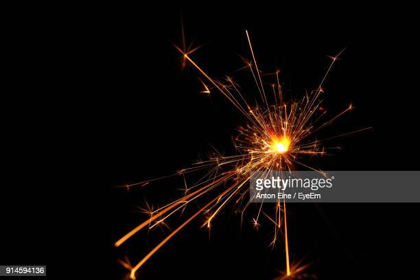 illuminated sparkler against black background - sparks stock pictures, royalty-free photos & images