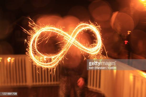 illuminated sparklers forming infinity sign at night - symbol stock pictures, royalty-free photos & images