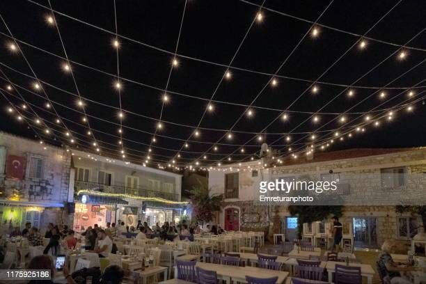 illuminated square with people sitting in the restaurants at alacati at night. - emreturanphoto stock pictures, royalty-free photos & images