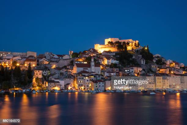 Illuminated St. Michael's Fortress and waterfront buildings at dusk, Sibenik, Sibenik-Knin, Croatia