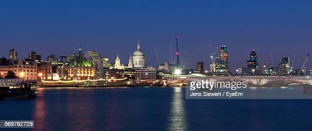Illuminated St Paul Cathedral Amidst Buildings By Thames River Against Sky At Night