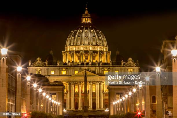 illuminated st peters basilica against sky in city at night - basilica stock pictures, royalty-free photos & images