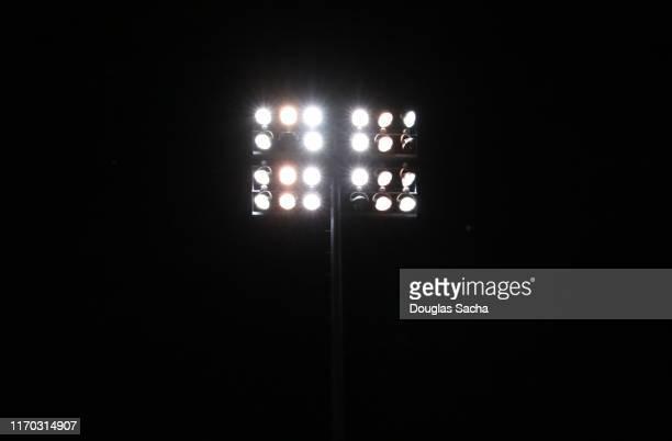 illuminated stadium lights on a dark sky - floodlit stock pictures, royalty-free photos & images
