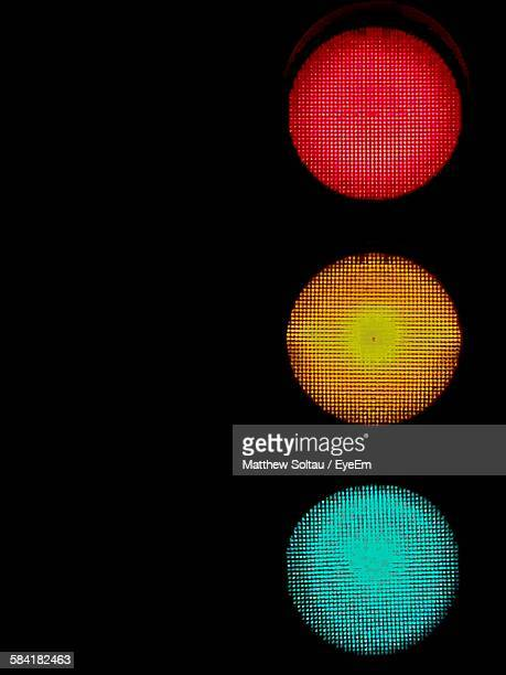 illuminated stoplights at night - road signal stock pictures, royalty-free photos & images