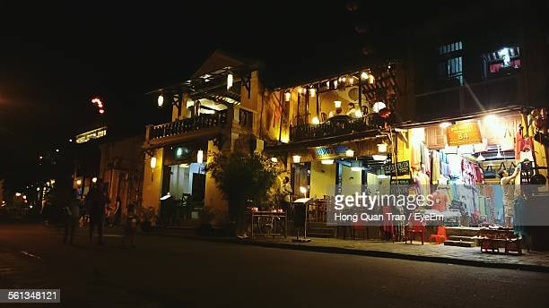 illuminated stores and restaurant by street at night - hong quan stock pictures, royalty-free photos & images