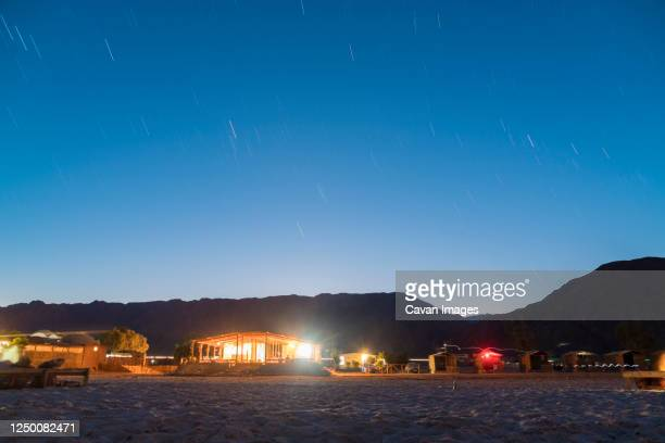 illuminated straw huts at nuweiba by the beach, south sinai at night - tourism in south sinai stock pictures, royalty-free photos & images