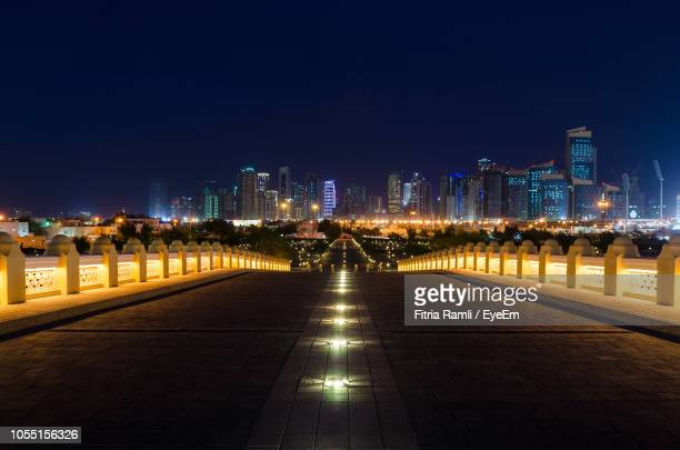 illuminated street amidst buildings against clear sky at night - doha stock pictures, royalty-free photos & images