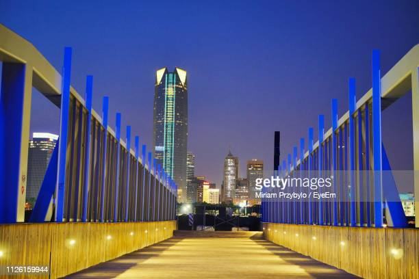 illuminated street amidst buildings against clear sky at night - oklahoma city stock pictures, royalty-free photos & images