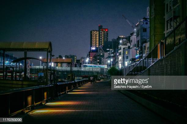 illuminated street amidst buildings against clear sky at night - seiichiro hayashi ストックフォトと画像
