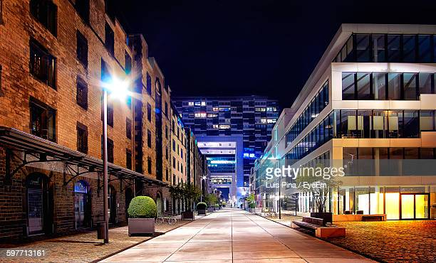 illuminated street amidst buildings against sky at night - fluchtpunkt stock-fotos und bilder