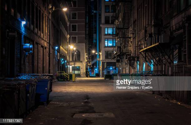 illuminated street amidst buildings at night - alley stock pictures, royalty-free photos & images