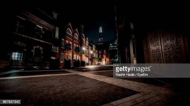 illuminated street amidst buildings at night - dark stock pictures, royalty-free photos & images