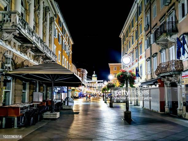 illuminated street amidst buildings in city at night - rijeka stock pictures, royalty-free photos & images
