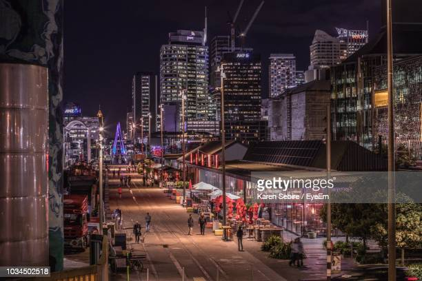 illuminated street amidst buildings in city at night - auckland - fotografias e filmes do acervo