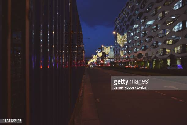 illuminated street amidst buildings in city at night - jeffrey roque stock photos and pictures