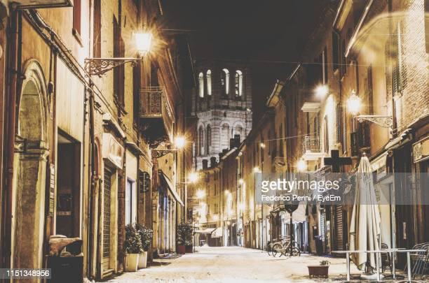 illuminated street amidst buildings in city at night - ferrara stock pictures, royalty-free photos & images