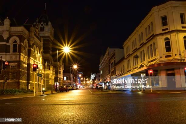 illuminated street amidst buildings in city at night - dunedin new zealand stock pictures, royalty-free photos & images