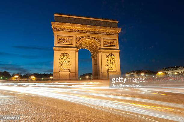 illuminated street by arc de triomphe at dusk - jens siewert stock-fotos und bilder