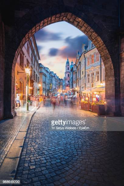 illuminated street by buildings against sky at sunset - prague stock pictures, royalty-free photos & images