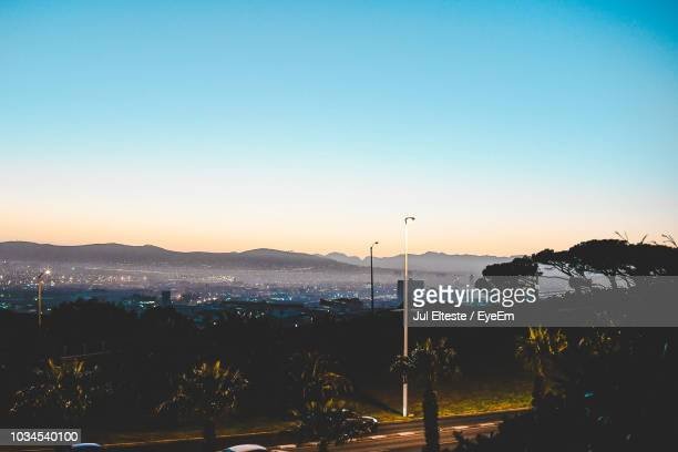 Illuminated Street By Silhouette Mountains Against Clear Sky At Sunset