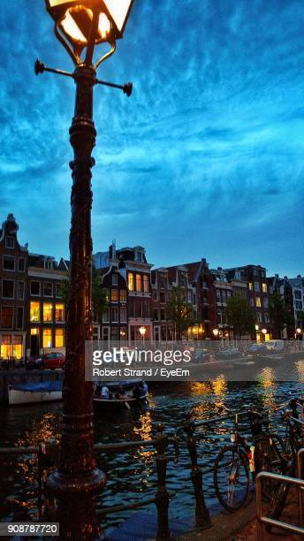 Illuminated Street Light By Canal In City At Dusk