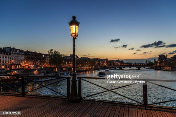 illuminated street light by river against sky at sunset - paris night stock pictures, royalty-free photos & images