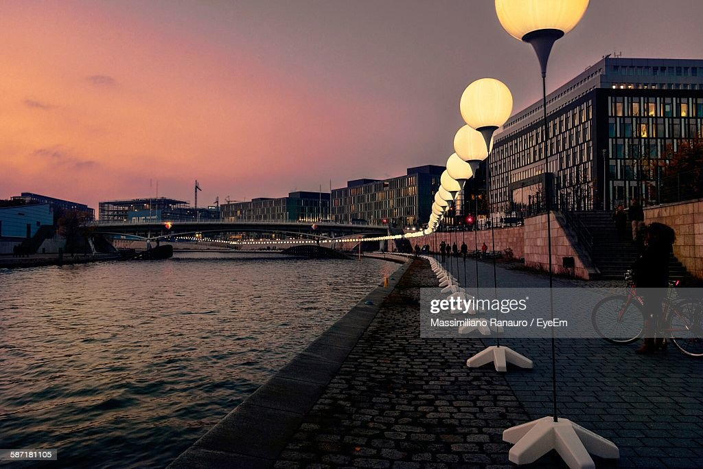 Illuminated Street Light By River At City Against Sky During Sunset : Stock Photo