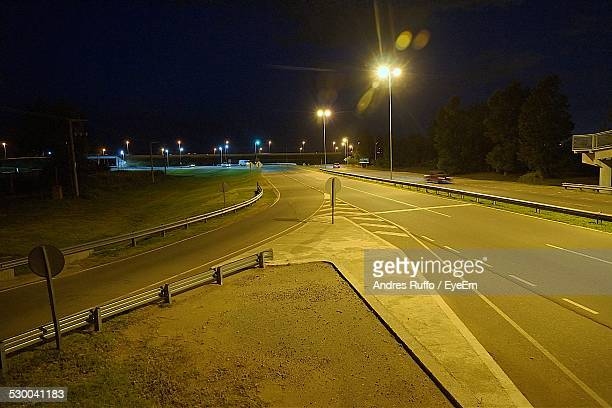 illuminated street light by road at night - andres ruffo stock pictures, royalty-free photos & images