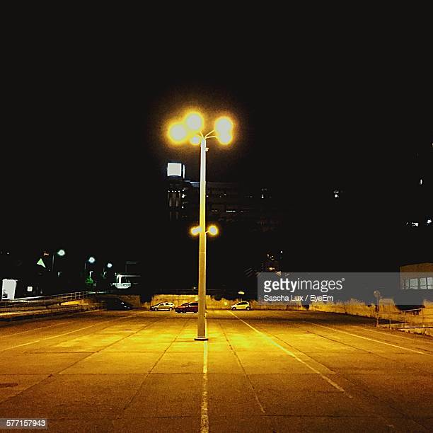 Illuminated Street Light In Parking Lot Against Clear Sky At Night