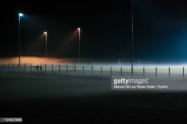 illuminated street light on field against sky at night - sport venue stock pictures, royalty-free photos & images
