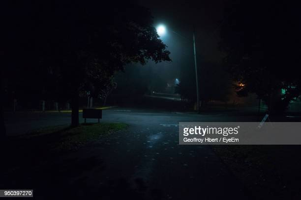 illuminated street light on landscape against sky at night - dark stock pictures, royalty-free photos & images