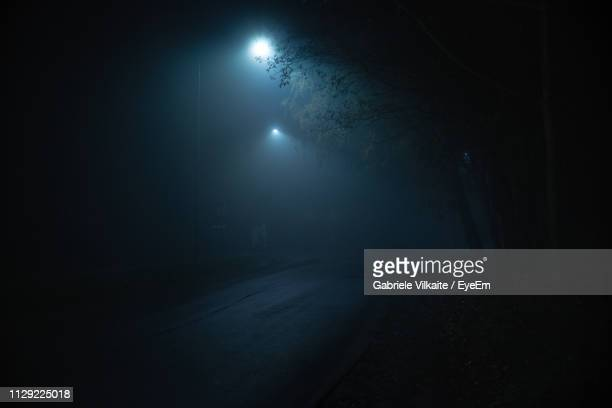 illuminated street light on road at night - spooky stock pictures, royalty-free photos & images