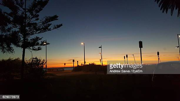 Illuminated Street Lights And Poles At Beach Against Sky During Sunset