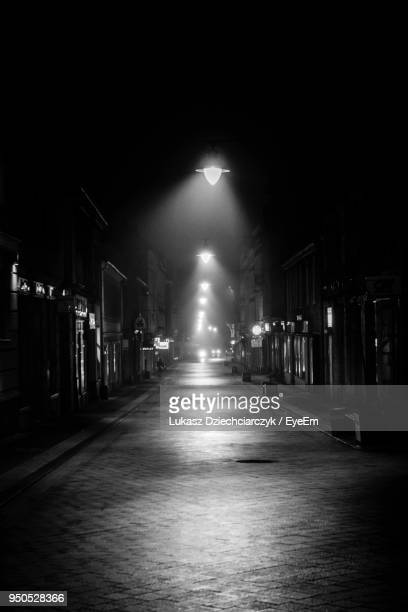 illuminated street lights at night - alley stock photos and pictures